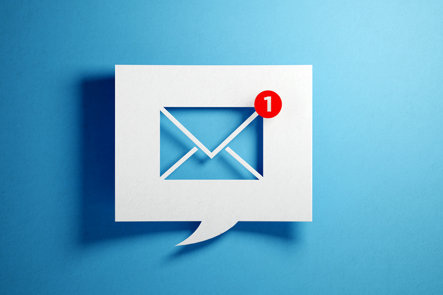 White chat bubble with email symbol on blue background. Horizontal composition with copy space
